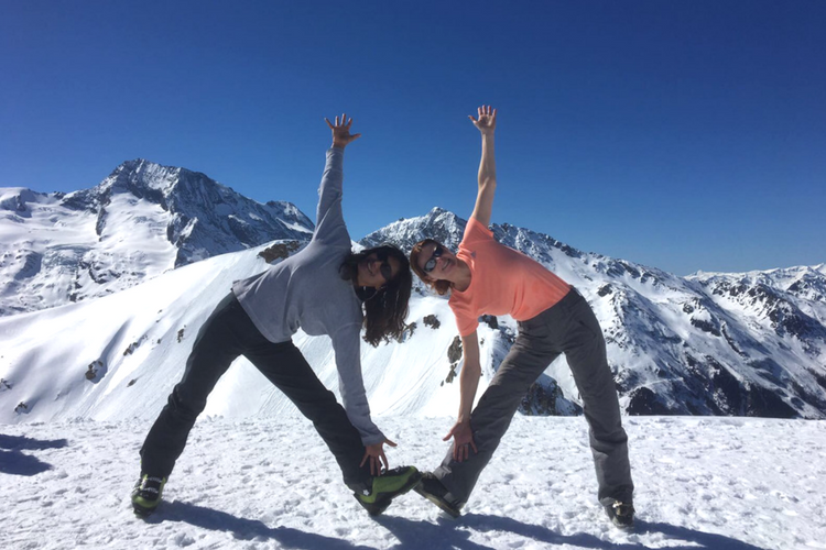 two guests triangle pose facing each other in the snow
