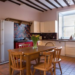 Thrupp venue kitchen with aga and table and 4 chairs