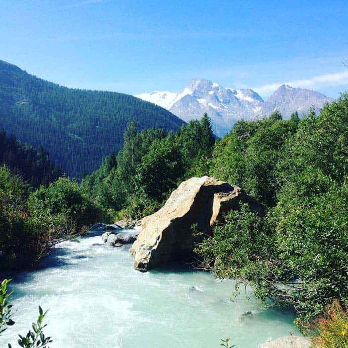 glacial melt water stream with big rock and mountain views France