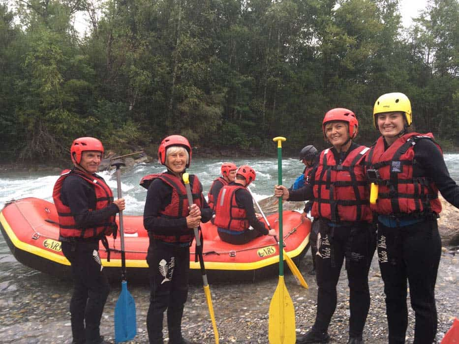 four people standing ready to go white water rafting with boat behind them