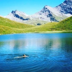 someone swimming in glacial lake French Alps