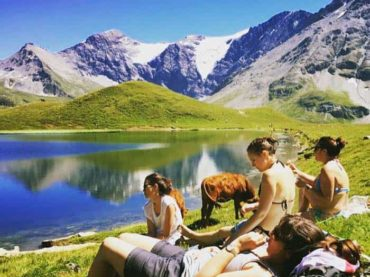 People sitting by glacial lake wit the cows