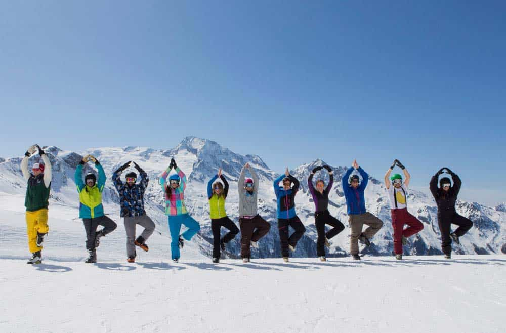 guests tree pose in a line on the slopes