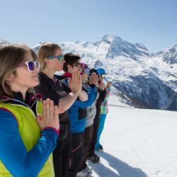 skiers in line in prayer pose