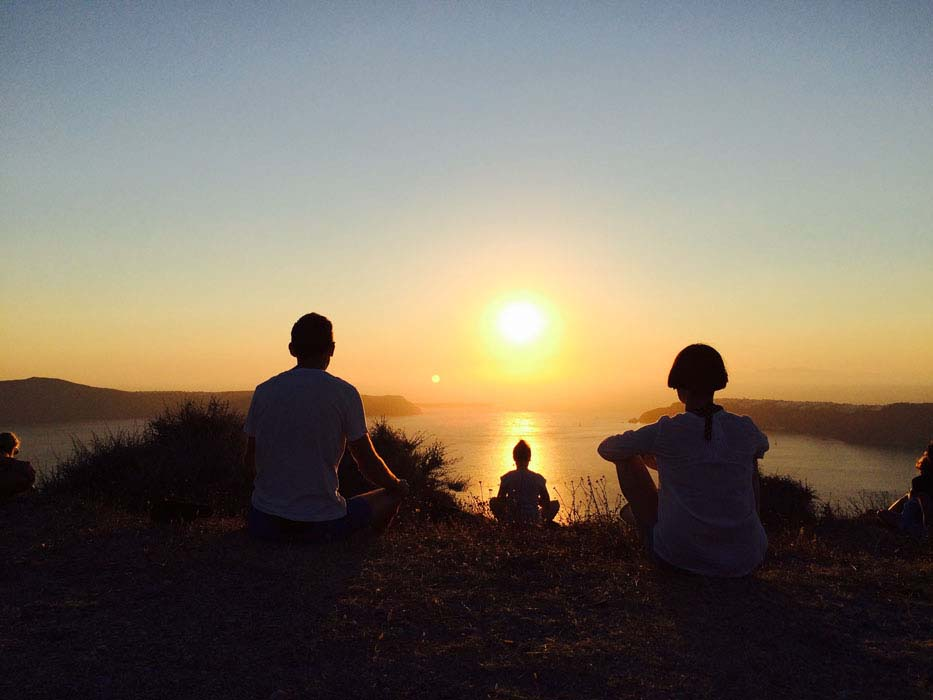Sunset overlooking caldera with three people silhouette