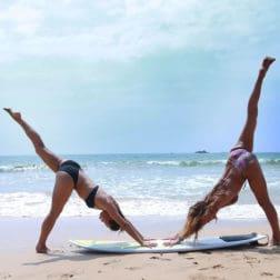 3 legged downward dog pose two girls surf board