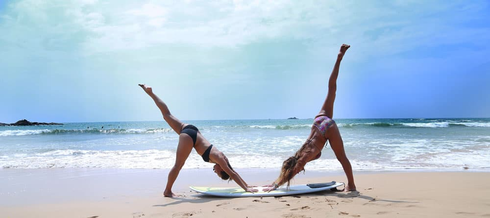3 legged downward dog pose two girls surf board