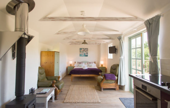The studio double bed windows kitchen in foreground new year yoga retreat cornwall
