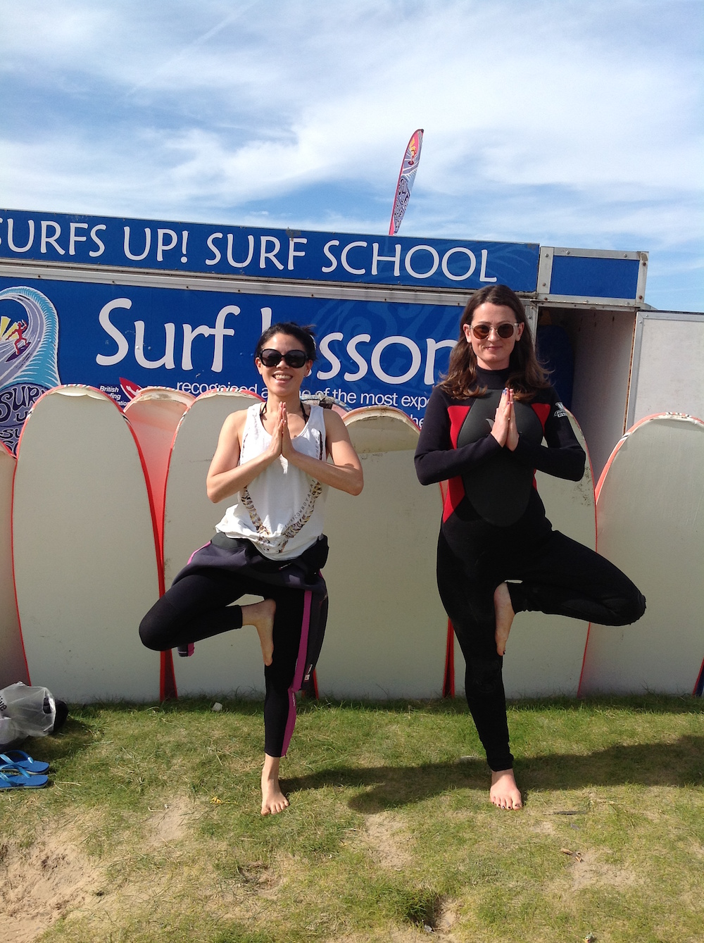 two girls tree pose in wetsuits surf yoga retreat cornwall