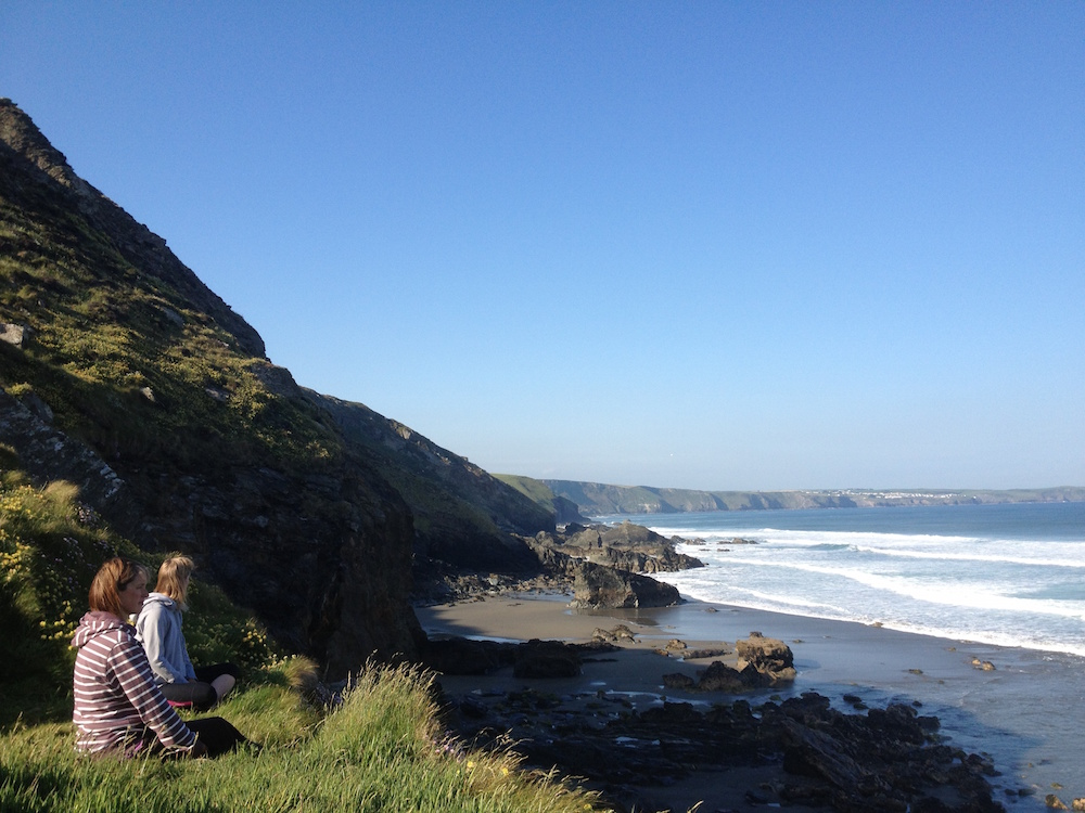 two people sitting meditation along coast surf yoga retreat cornwall