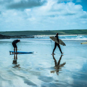 surfers carry boards on beach surf yoga retreat cornwall