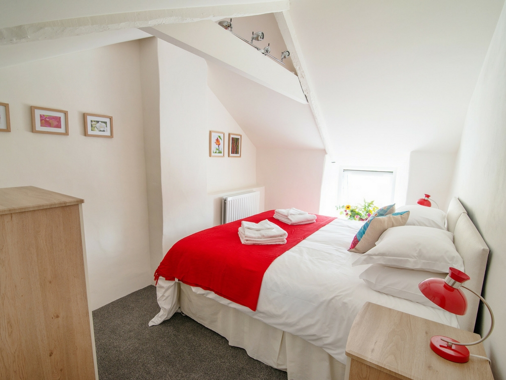 Bedroom Farmhouse - bed and red throw on bed august bank holiday yoga retreat Cornwall