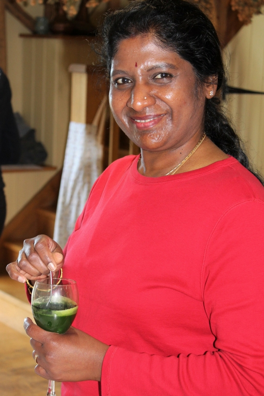 guest with green wheatgrass shot smiling