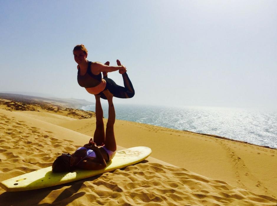 sandboarding and partner yoga work sand dunes morocco