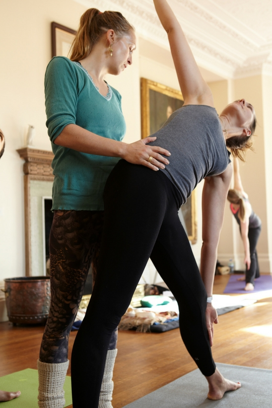 yoga teacher adjusting student in triangle pose