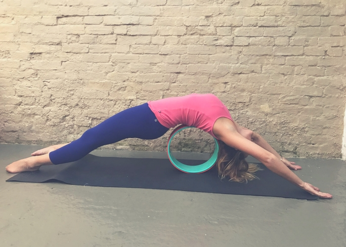 stretching out front side of body on yoga wheel