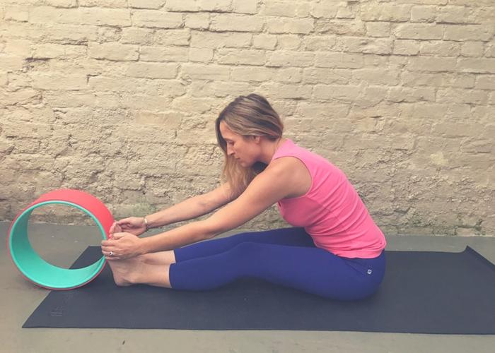 forward bend using yoga wheel