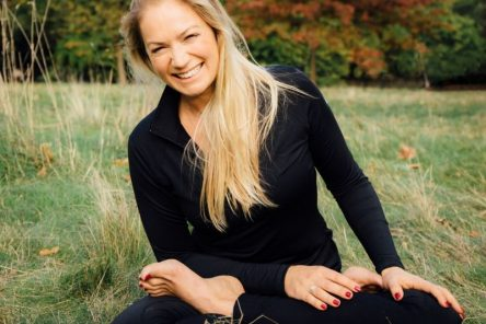 Yoga teacher Laura McBride is sitting cross legged smiling
