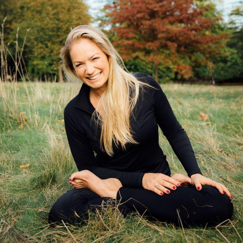 Yoga teacher Laura McBride is sitting cross legged smiling