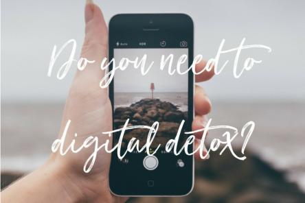 hand holding phone sea behind digital detox