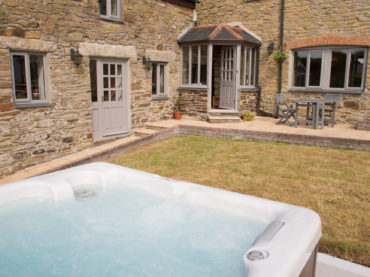front of farmhouse outdoor hot tub new year yoga retreat cornwall