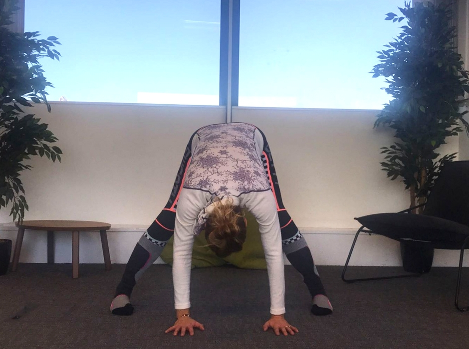 person doing wide legged forward bend yoga pose
