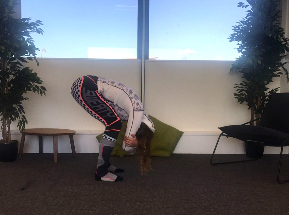 person doing forward bend with knees bent