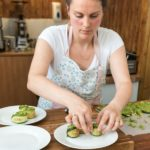 chef charlotte making cucumber vegan sushi on plate