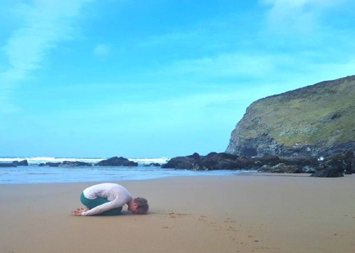 childs pose on the beach in cornwall cliffs and sea
