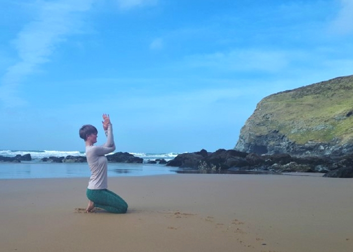 seated eagle yoga pose on beach cliffs and waves cornwall