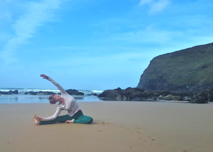 seated side bend on beach cliffs and sea cornwall