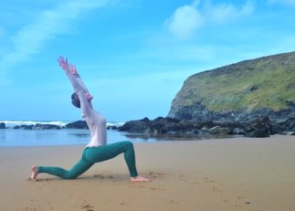 kneeling lunge yoga surfers beach cornwall cliffs sea