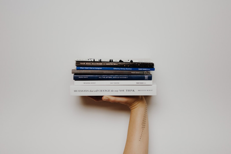 hand with books balanced on it