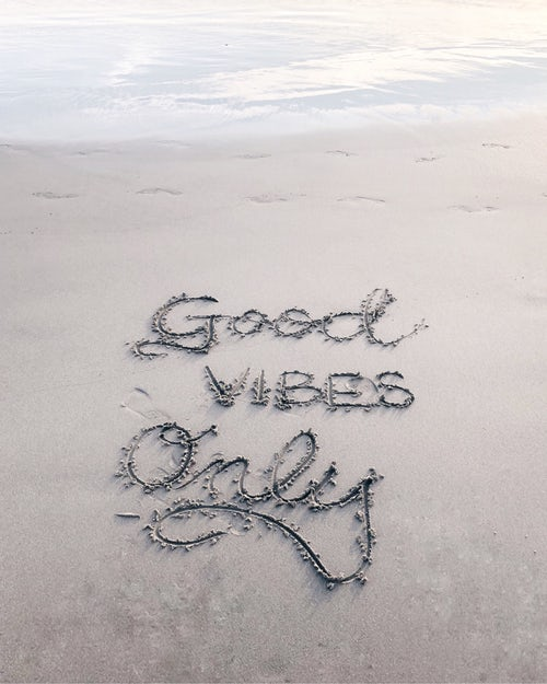 good vibes written in sand