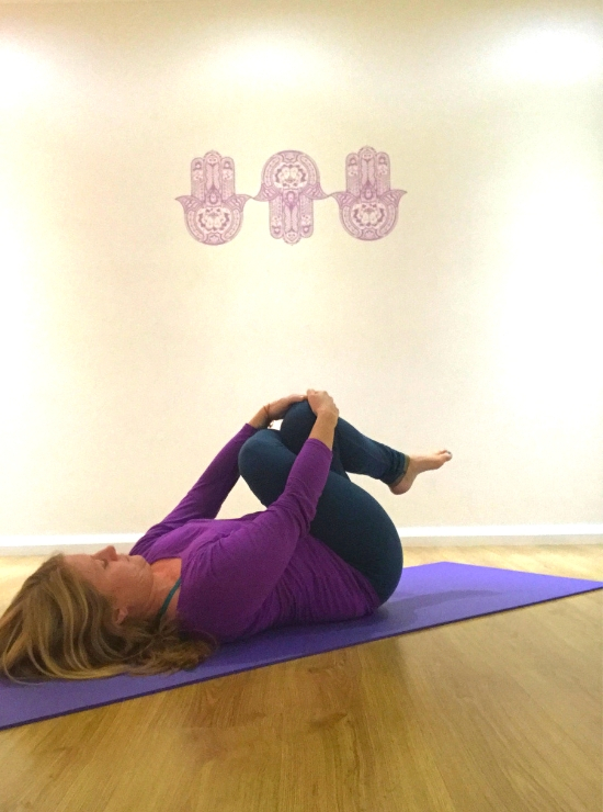person lying on back legs crossed pulled into chest yin yoga pose ease back pain