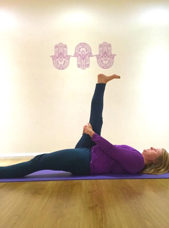 person lying on back foot to sky yin yoga pose ease back pain