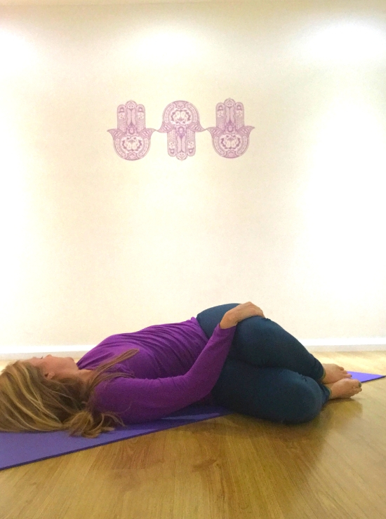 person twisting legs to the right head to left supine twistyin yoga ease back pain