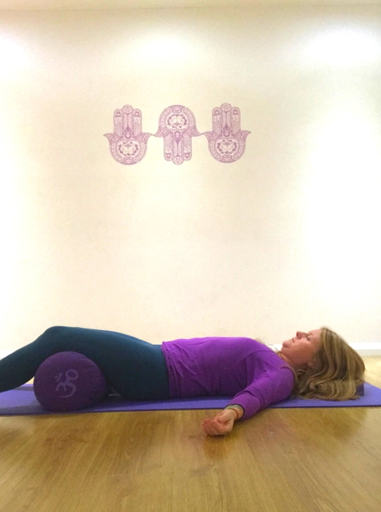 caterpillar yin yoga pose person lies on back legs over bolster helps burnout