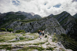 people standing on outdrop in mountains yoga holiday montenegro