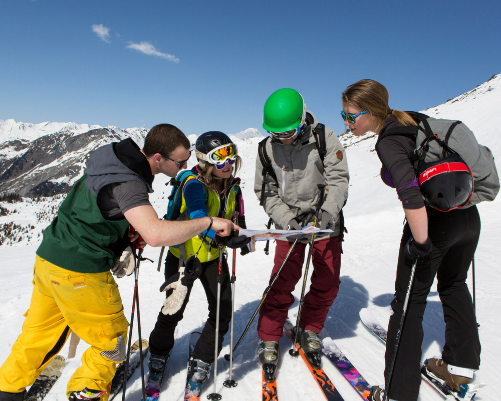 Four skiers looking at map
