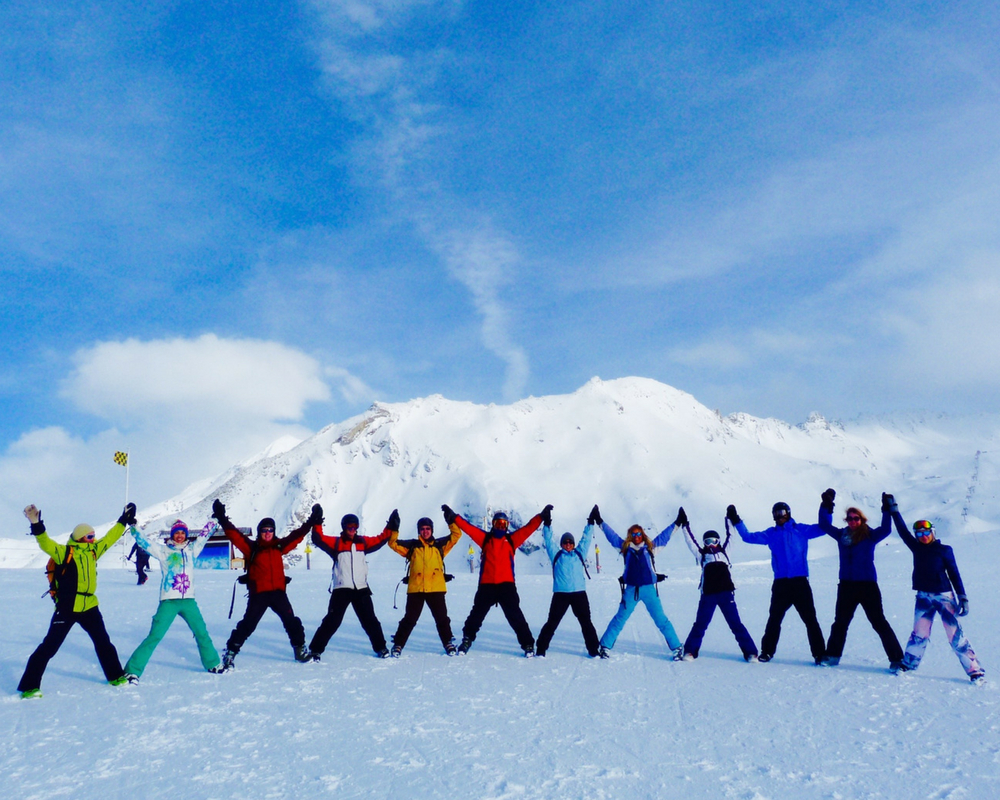 Line of skiers with hands up