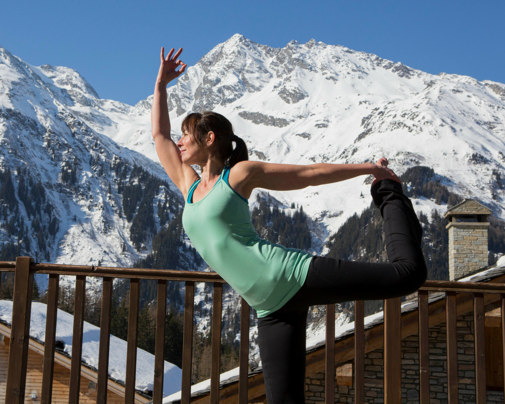 Yogi pose on balcony with snow in background