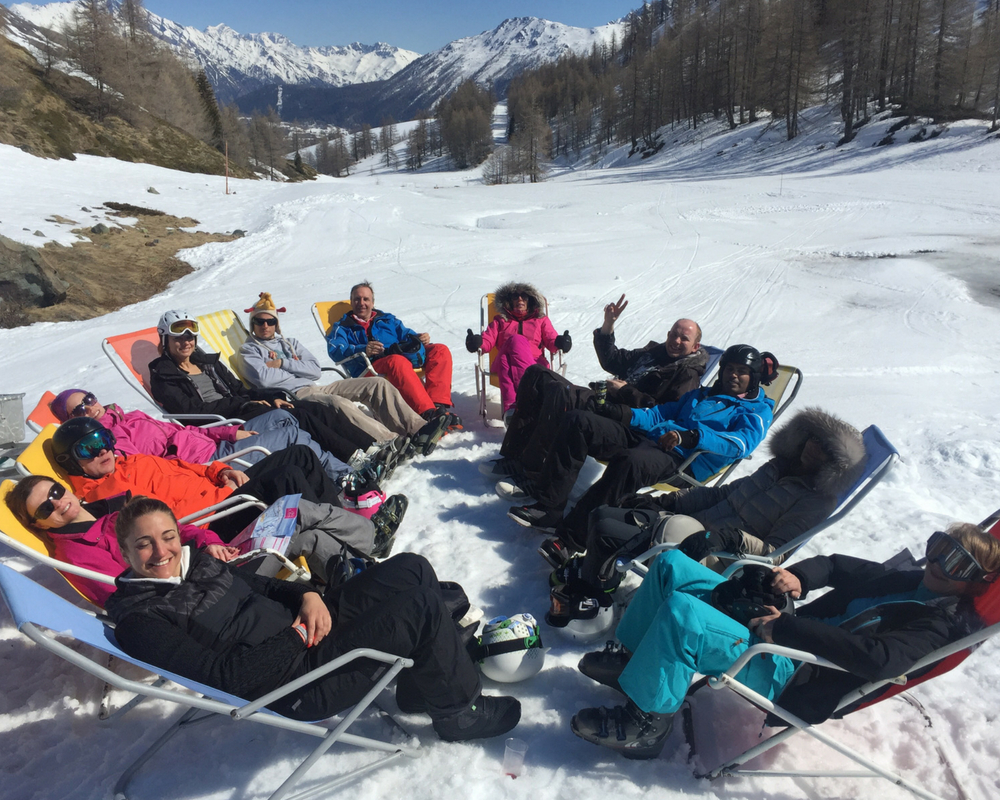 Skiers seated in deck chairs on snow