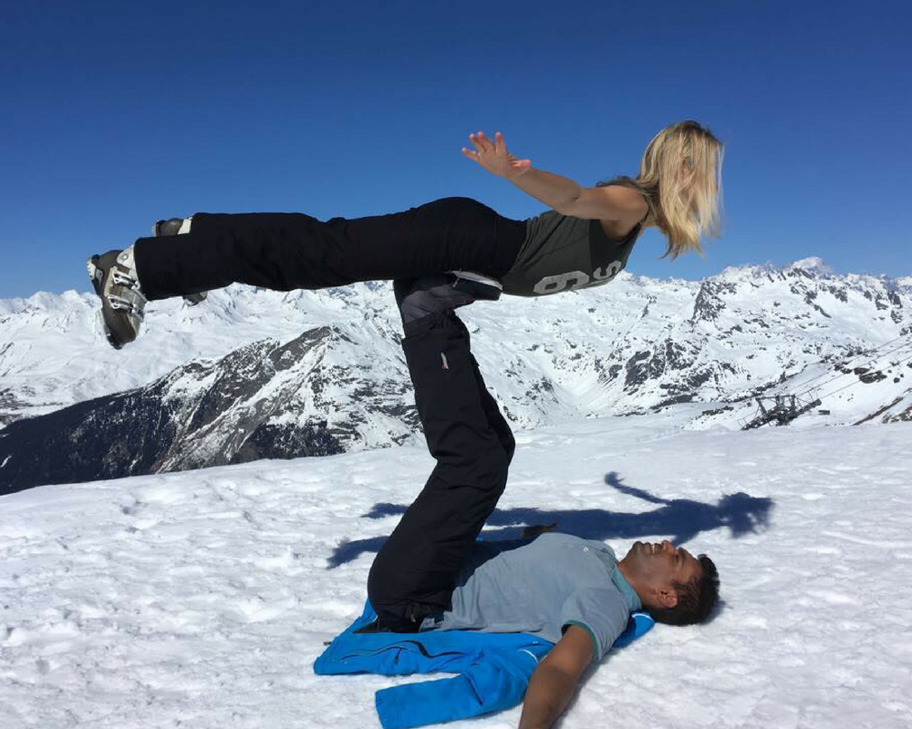 partner yoga pose with two people in snow