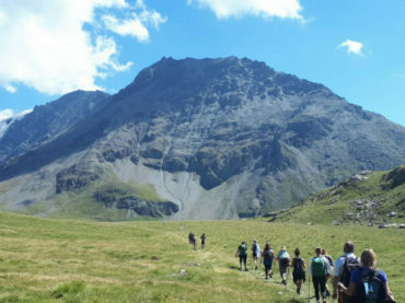 Line of walkers heading towards mountains