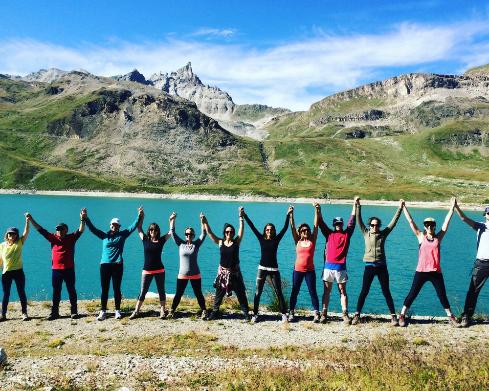 Line of yogis with hands up in front of lake