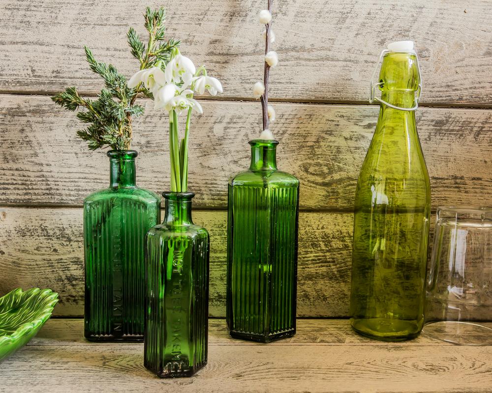 Green glass bottles with flowers in - august bank holiday yoga retreat norfolk