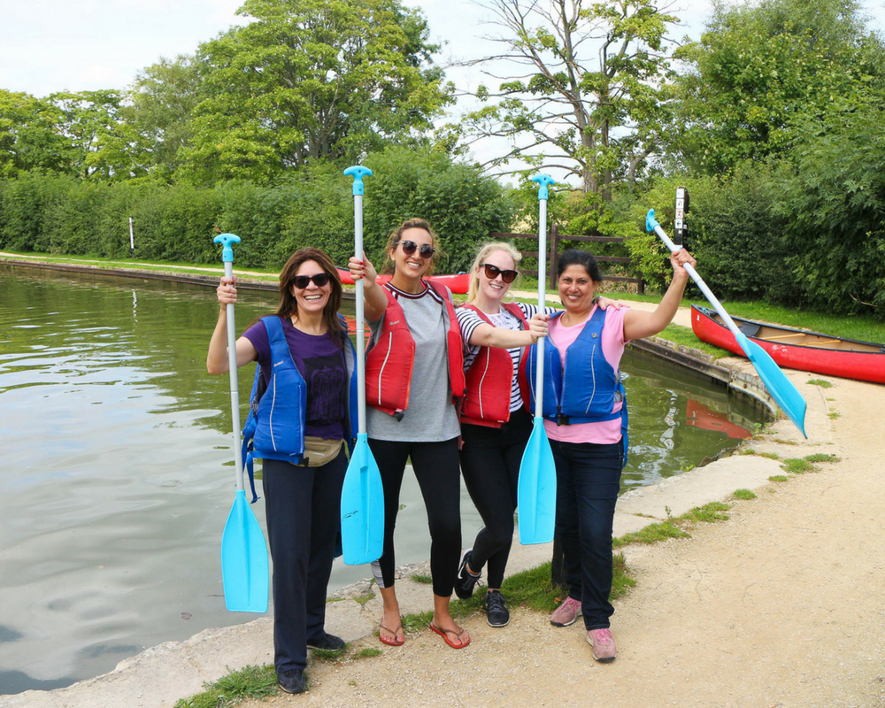 Four canoeists with paddles August yoga retreat