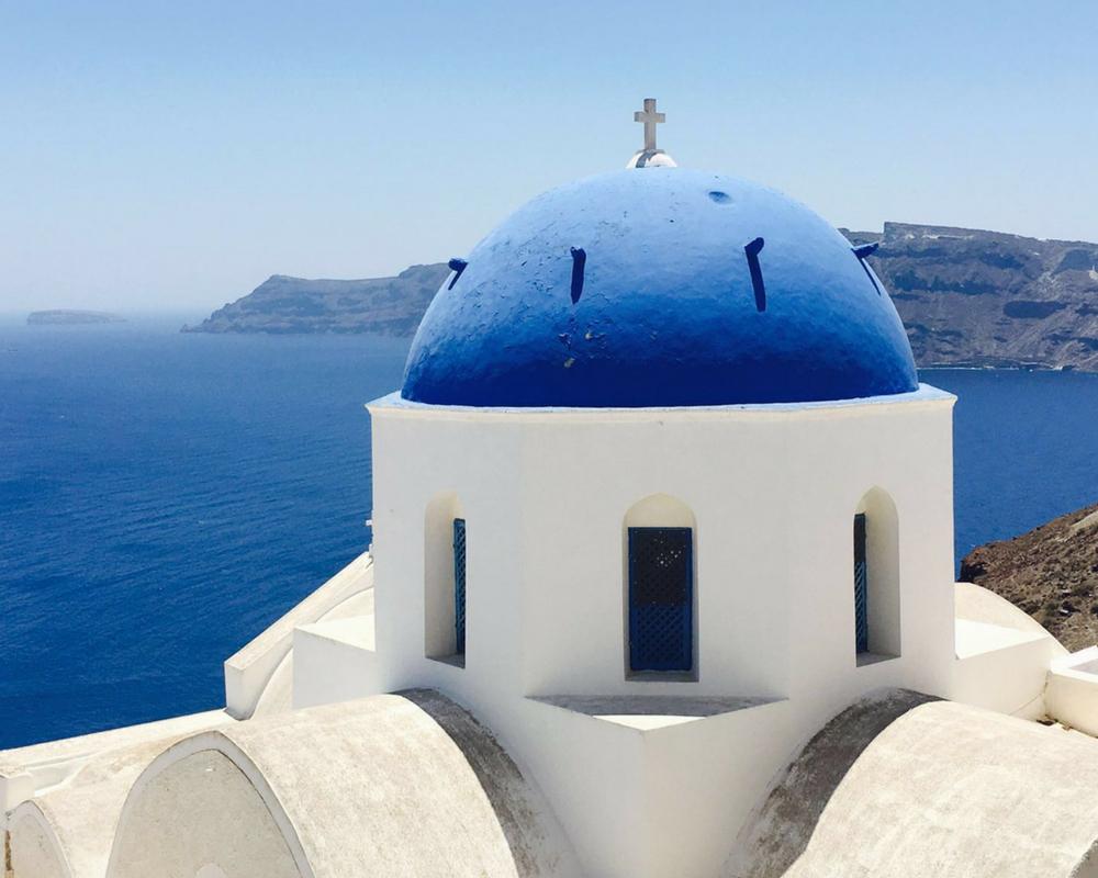 Greek blue domed church overlooking sea