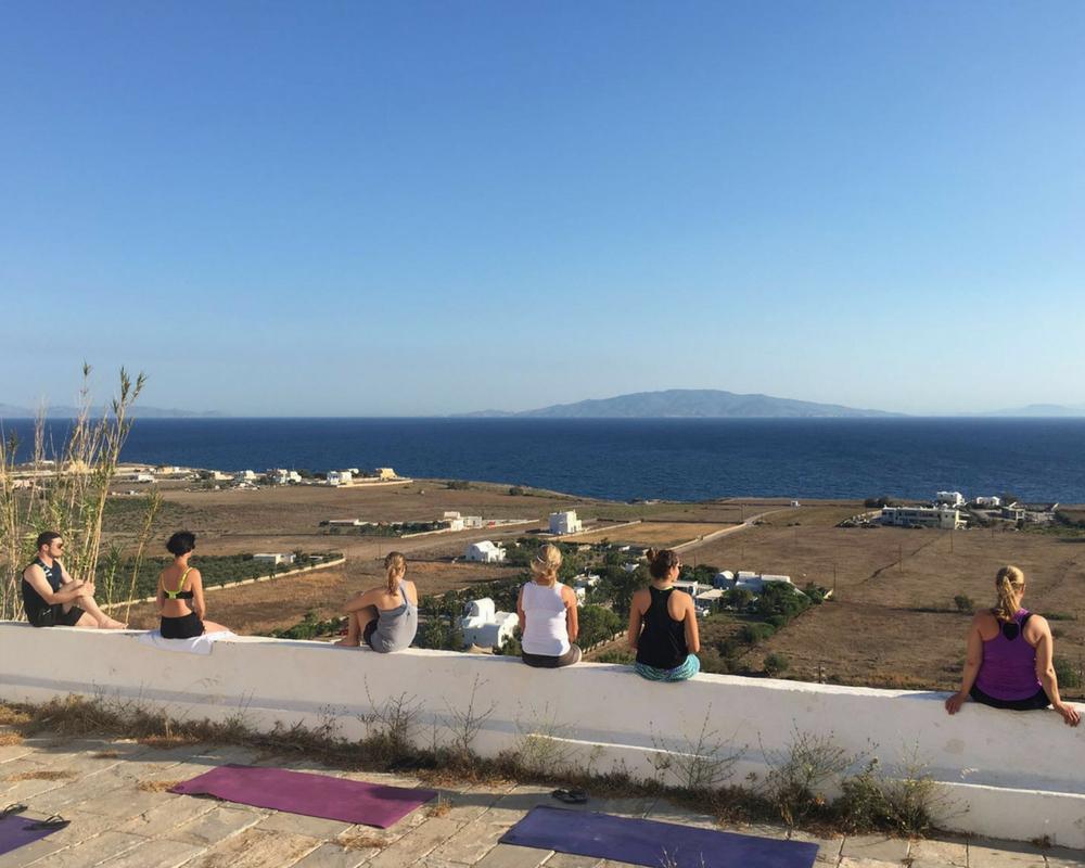 Yogis meditating on wall overlooking sea